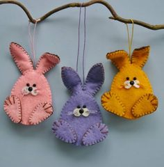 drei genähte Osterhasen, jeder in verschiedener Farbe, Lila, Rosa und Gelb, Ostergeschenke basteln
