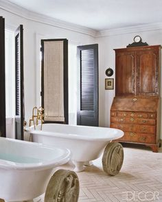 Architectural fragments are displayed in front of a pair of bathtubs salvaged from the Russian embassy; the shutters were designed by Carter, and the secretary is 18th century.