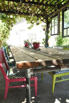 Vintage windows hung from trellis, dining table made from reclaimed redwood and galvanized pipes.