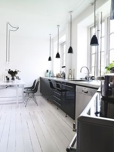 KITCHEN: Shiny black cabinets, white counter, white wood floor, stainless steel appliances, white painted walls