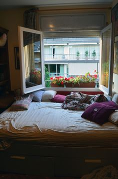 Mattress-like, comfy layers - down looking, lots of pillows, pretty big so that takes most space against window-wall. Also love flowers on window sill.