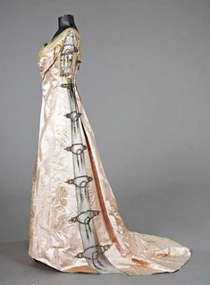 Ball gown, circa 1900, with signature label to waistband, of pink damask satin woven with large bearded irises and swags of interlaced ribbons, the side panels and sleeves inset with tulle panels embroidered in metal threads and diamanté studs.