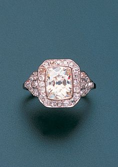 An art deco diamond ring, circa 1920  The central cushion-shaped diamond within an octagonal border and between shield-shaped shoulders set throughout with old brilliant-cut diamonds, principal diamond approximately 2.60 carats,