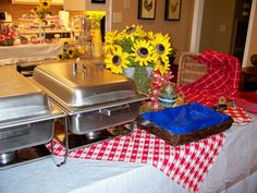 View of BBQ serving table.  Sunflower arrangement made to compliment picnic decor.