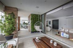 Apartamento localizado no Itaim com 330m² com uma ampla varanda de estar. Depois de ter sido fechada com portas de correr de vidro, a varanda tornou-se mais funcional. O resultado é um ambiente claro, que oferece o conforto e estilo, tendo um cenário diferenciado com o lindo jardim vertical com plantas da espécie Jiboia.
