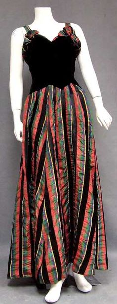 Late 1930s evening gown in plush black velvet and plaid taffeta. Fitted, slightly elongated velvet bodice with plaid taffeta bow topped cuff and straps. Gown has a sweeping, full skirt. Via Vintageous.