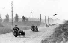 """Climate extremes in Russia contributed keenly to the defeat of the German invasion. Here, Waffen SS motorcycle recon troops speed down a dirt """"motorway"""" in western USSR during the early phases of Barbarossa. This """"motorway"""" would become a sea of mud in the autumn -- and disappear completely during winter under snow and ice, the telephone poles the only indication that it existed."""