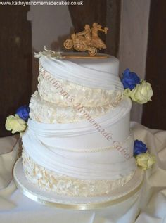 3 Tier wedding cake with oak leaves and swag detail.  Fresh roses. Amazing wood motorbike cake topper,  carved by the bridegroom, a professional stone mason