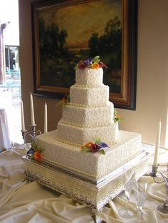 This 5 tier cake has a swirl design and a piped border on all tiers! Sugar tulips were used for the topper and throughout the cake for added color ! This cake serves 315