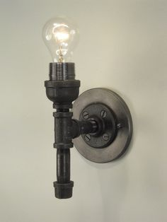 diy sconce | DIY / Wall sconce made with black pipe.