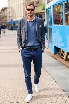 Shop this look on Lookastic:  https://lookastic.com/men/looks/blazer-v-neck-sweater-long-sleeve-shirt-chinos-low-top-sneakers-pocket-square-belt/1631  — White Long Sleeve Shirt  — Grey Polka Dot Pocket Square  — Blue V-neck Sweater  — Grey Wool Blazer  — Black Leather Belt  — Navy Chinos  — White Low Top Sneakers