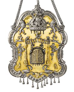 A POLISH PARCEL-GILT SILVER TORAH SHIELD rococo cartouche form, central compartment with Torah scrolls and openwork doors flanked by columns supporting a balustrade topped by a deer and lions, flanked by running deer, flowers, and swans, below rampant lions holding a crown also topped by a deer, with hanging tassels and chain. marked near base KL and 12. height 12 1/2 in. 31.8 cm circa 1840