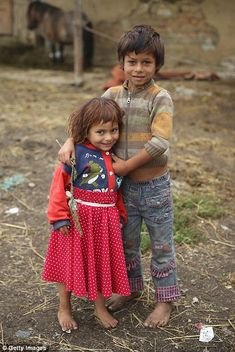 Local Romanian gypsy children Calin Istvan, right, and Rocsana Nicoleta Varga pause for a photo