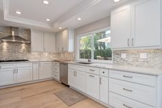 Light and bright kitchen with full backsplash, range hood, white cabinets and under cabinet lighting.