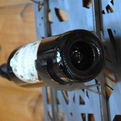 Vinställ i laserskuren industriell look, borstad plåt, plats för 5 flaskor.  Levereras i platt paket som enkelt skruvas ihop med 6 skruvar.