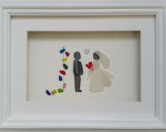 Heres the ideal gift for the couple on their wedding day - truly original and personal to the bride and groom. Many of the people who have received these portraits as gifts have described them as the best present ever and I couldnt be more delighted.  This sea glass bride and pebble groom are set inside a 35cm x 35cm glazed box frame in either black or white. (other sizes and designs are available in my shop)  Date and names can be added to the mount and some personalisation to the picture…
