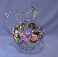 This heavy glass pitcher has been hand painted with a beautiful vine of pink roses, purple hydrangeas, green leaves and dark blue butterflies.
