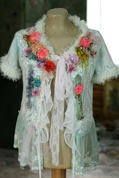 Whimsy colorful light cardi, altered couture, hand dyed in shades of pale turquoise, aqua, sage; richly embellished with intricate details. The hems and half of the back is adorned with white beads and sequins, The bold collarline is adorned with cottons and tulle, old lace pieces, -stitched, textured, and adorned with ivory pearls, handmade silk and satin roses, purple petals and vintage trims. The jacket fastens with soft lingerie lace ribbons. Will look great with jeans and simple white…