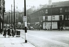 A busy streetscene at the south end of Garscube Road, looking south-east along Cowcaddens Street towards the city centre with New City Road leading off to the right. The entrance to Cowcaddens Underground Station is beside the Subway Bar.  The photograph was taken in 1964, when New City Road was a busy thoroughfare connecting Great Western Road with the city centre.   The entire Cowcaddens area was redeveloped a few years later, with all of the buildings in the photograph being demolished.
