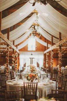 Perfect wedding decor. String lights, white linens, wood beams, and chandeliers. Beautiful barn wedding!