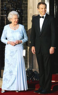 2002 Queen Elizabeth posed with then British Prime Minister Tony Blair in a pleated periwinkle gown and sapphire jewelry.