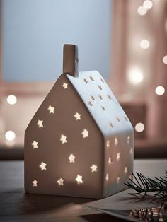 Featuring a little chimney and starry cut out details, our house shaped tea light holder is crafted from unglazed white porcelein. Petite and delicate, its little starry windows allow the perfect soft glow to shine through and is the perfect subtle nod to the festive season. Comes with matching base (not pictured).
