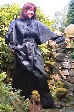 Looking lovely in a black rubberlined satin mac with a short shoulder cape