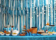 Here's a fantastic buffet display for an Under the Sea birthday party designed by Nice Party.   I am in love with that backdrop!  The assymetry of the ribbon, and circle banner mimics the movement of the ocean, and water bubbles.  The pops of color in the orange 'starfish' and napkins adds dimension and interest, while the adorable fish cut-outs add …