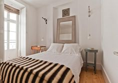 The striped blanket on the bed is made with sheep's wool bed woven in a traditional Portuguese style.