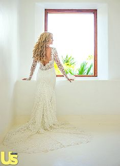 The bride's wedding dress boasted long, lace sleeves, an open back, and a chapel train, which trailed behind her as she walked down the aisle.