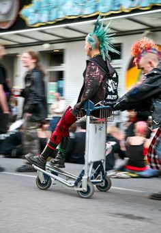 Two punks with mohawks riding on a luggage cart
