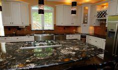 3 ultimative Granit führen die Äderungen und kreisförmige Muster dieses dunkle Braun Granit zeichnen das Auge auf die große Küche-Insel. Eine rote Glas Fliesen Backsplash zieht wärmere Farben den dunkler Granit, während die weißen Mobiliar die Küche hell und luftig hält.