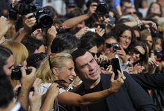 American actor John Travolta, smiles for the camera as he poses with a fan at the conclusion of a photo call promoting his new film 'Savage' at the 60th San Sebastian Film Festival Cinema in San Sebastian, Spain, on September 23, 2012.