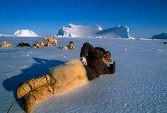 Polar Inuit hunter relaxes on frozen Baffin Bay, Greenland