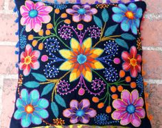 Vibrant, colorfull flowers pop beautifully from the dark blue background of this hand embroidered cushion. Fantastic textures of needlework from the Andes to your home.  Our pilllows are first woven on a traditional loom with sheep wool and later adorned with beautiful embroidered flowers made of alpaca wool. A playful crochet trim gives this cushions the perfect finish. The texture of sheep wool is thick an makes a sturdy and durable cushion.  Back zipper clousure. Measures 16 in x 16 in…