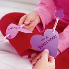 """Sweet Hearts Pixy Stix: Cut a heart from card stock (3.5 in x 3.5in) Punch 2 holes in heart (1 toward upper right & other toward lower left). Use markers to write message """"To A Sweetheart"""" Insert Pixy Stix through holes. Sticker 2 heart shaped stickers to form arrowhead."""