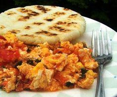 Un típico desayuno colombiano: huevos revueltos con tomate y cebolla.