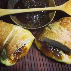 Croissant tostado con queso fundido y cebollas caramelizadas.
