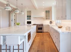 Nantucket Home with New Coastal Interiors. Sleek white kitchen. Paint color is Benjamin Moore, White Dove.