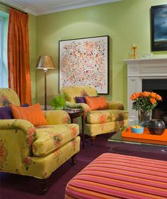 This green living room has orange and purple accents throughout the space. These three colors are an example of Triadic color schemes. When you put these colors together they bring a lively feeling in the room.