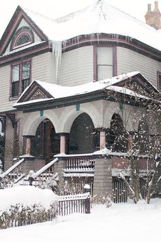 This snowy victorian house looks so stately in the snow.