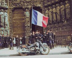 A French mademoiselle waves the French Tricolor in tribute to the forces which liberated her city as they march past the Notre Dame Cathedral in Paris, France. 26th August 1944