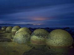 The Moeraki Boulders, New Zealand, are huge spherical stones that are scattered over the sandy beaches, but they are not like ordinary round boulders that have been shaped by rivers and pounding seas.
