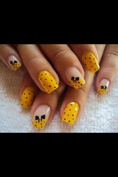 Pretty yellow and black nail design with a cute little black bow