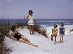 Four women walk and recline on a beach along the Gulf of Mexico          j baylor roberts