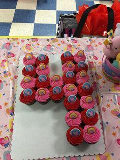 Peppa Pig number 4 cupcake cake with Peppa Pig rings on top.
