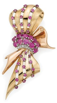 *Two-Color Gold, Platinum, Ruby and Diamond Bow Clip Yellow and rose gold, the stylized bow centering 11 round and oval rubies approximately 5.00 cts., edged on one side by 8 round diamonds, the pierced scrolled ribbons highlighted by 28 small round rubies, circa 1940. ( Late Art Deco-Early Retro)