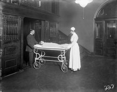 mortisia:   Nurse and orderly transporting a child on a stretcher to the operating room at the Hospital for Sick Children, c. 1915
