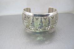Stunning vintage, heavily stamped Sterling Silver cuff bracelet by Navajo artist, Michael Tahe. Bracelet featuresa row of Medicine men
