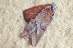 An adorable newborn boy romper with wooden button details and silk chiffon tiesSuitable for a smaller newborn